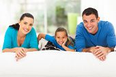 happy young family lying on bed with their pet dog at home
