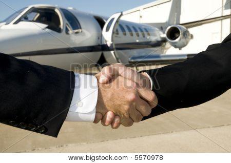 Постер, плакат: Бизнесмены пожимая руки перед корпоративным Jet, холст на подрамнике