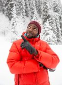 African American Cheerful Man In Ski Suit In Snowy Winter Outdoors