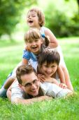 picture of family fun  - Young Family Lying on the Grass in Park - JPG