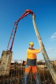 builder worker standing near trailer-mounted boom concrete pump on metal rods reinforcement of concrete casting formwork