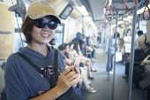 face of woman in sky train with smart phone in hand use for city life and traveling theme