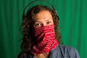 picture of buff  - Young girl with curly hair is enjoying music from headphone with a covered face with buff - JPG