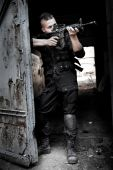 stock photo of m4  - Aiming man with M4 rifle on the ruined building background - JPG