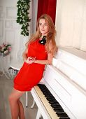 The Attractive Young Woman In A Red Dress Stands Near The White Piano, In Home Interior