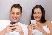 hotel, travel, relationships, technology, intermet and happiness concept - smiling couple in bed with smartphones