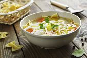 picture of ceramic bowl  - Chicken soup with pasta Farfalle in the bowl on the table - JPG
