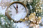 Clock with fir branches and Christmas decorations under snow close up