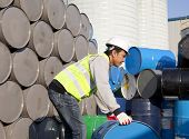 picture of bio-hazard  - Factory worker on working standing between stacking drums - JPG
