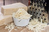 foto of shredded cheese  - Heap of fresh Parmesan Cheese on wooden background - JPG
