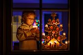 Little Boy Standing By Winter At Christmas Time And Holding Candle