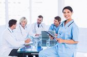 Smiling female surgeon holding reports with colleagues in meeting at a medical office