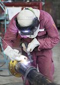 image of pipe-welding  - Craftsman in a safety suit is welding a metal pipe - JPG