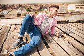 young casual man in a fashion pose lying on the roof top of a building