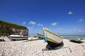 Boats at the beach of Yport, Normandy, cliffs of the Alabaster Coast in background