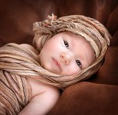 Closeup portrait of cute newborn baby girl lying down on the bed and covered with stylish beige shaw