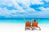 Two happy people having fun on the beach, sitting on comfortable sunbed with raised up hands for joy