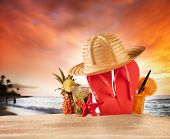 Summer beach with red sandals, drinks and accessories