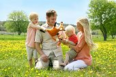 Happy Family Of Four People Playing With Toys Outside In Flower Meadow