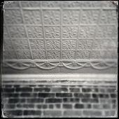 Instagram style image of an old tin ceiling tiles and brick wall