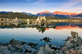 The magic of Mono Lake. Outliers - calcareous tufa formation  on the smooth water of the lake. Orange sunset