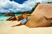 Woman at beautiful beach wearing rash guard. Seychelles, Praslin, Anse Lazio