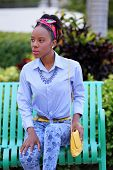 stock photo of jamaican  - Stock image of a Jamaican female model sitting on a bench - JPG