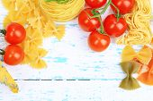 Different pasta, cheese and tomatoes on wooden table close-up