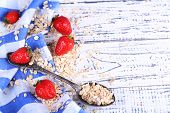 Strawberries with oatmeal and vintage spoon, on color wooden background