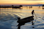 stock photo of fishermen  - silhouette of fishermen with yellow and orange sun - JPG