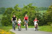 stock photo of bike path  - Family with children having a weekend excursion on their bikes on a summer day - JPG