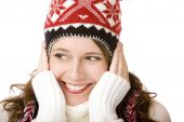 Young Attractive Smiling Woman With Cap And Scarf Holding Her Cheeks In Wintertime