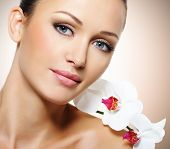 Beauty face of  beautiful woman with a white flower. Skin care treatment.