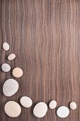 Light Pebbles On Wooden Ebony Tree Background