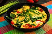 Omelette with asparagus and tomato on frying pan