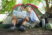Cute couple sitting by tent reading a map on a sunny day