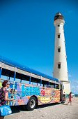 ARUBA, CARIBBEAN - DEC 2013: Picture of California Lighthouse Landmark with colorful bus in fron on