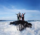 Three business people wearing superhero costumes posing on a rock with gushing waves.