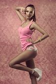 picture of ponytail  - sexy brunette girl with fit body posing in fashion portrait with spring colorful style pink shirt colorful panties ponytail and wrist watch - JPG