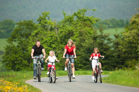 image of exercise bike  - Family with children having a weekend excursion on their bikes on a summer day - JPG