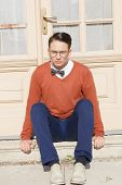 Serious Handsome Man With Glasses And Sweater Sitting On Steps In Front Of House And Posing