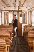 Serious Man In Suit With Glasses Posing And Trying To Enter In An Old Train Wooden Wagon
