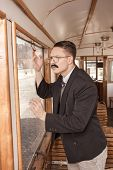 Surprised And Shocked Man With A Mustache In A Suit With Glasses Posing In An Old Train Wagon