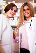 Two Young Pharmacist Woman Behind The Desk