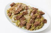 Beef, cooked with onion and spices and served on a bed of frikeh, fire-roasted green wheat, an Arab recipe.