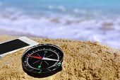 Compass And Mobile Phone On The Beach