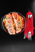 fresh fried natural pink salmon on italian traditional tagliatelles backed with tomato and vegetables served over black wooden table high resolution