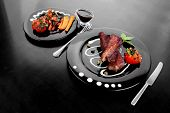fresh red beef meat steak barbecue garnished vegetable salad sweet potato and basil on black plate over black wooden table with bbq sauce in sauce boat high resolution hidef