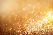 Christmas Background. Golden Holiday glowing Abstract Glitter Defocused Background With Blinking Stars. Blurred Bokeh