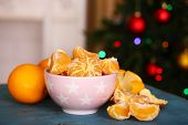 pic of tangerine-tree  - Sweet tangerines and oranges on table on Christmas tree background - JPG